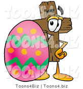 Illustration of a Cartoon Christian Cross Mascot Standing Beside an Easter Egg by Toons4Biz