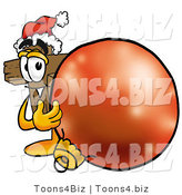 Illustration of a Cartoon Christian Cross Mascot Wearing a Santa Hat, Standing with a Christmas Bauble by Toons4Biz