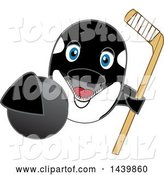 Vector Illustration of a Cartoon Killer Whale Orca Mascot Grabbing a Hockey Puck and Holding a Stick by Toons4Biz