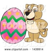 Vector Illustration of a Cartoon Lion Cub School Mascot with an Easter Egg by Toons4Biz