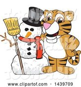 Vector Illustration of a Cartoon Tiger Cub Mascot with a Snowman by Toons4Biz