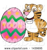 Vector Illustration of a Cartoon Tiger Cub Mascot with an Easter Egg by Toons4Biz